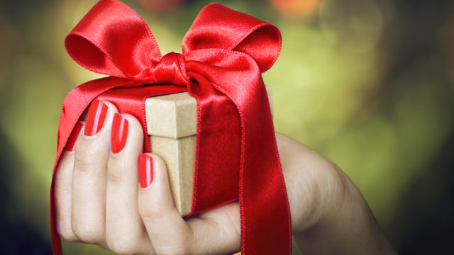A hand holding Christmas gift tied with red ribbon