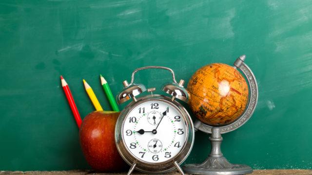 alarm clock, apple and globe on school desk background